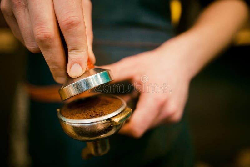 Pigiatura del caffè espresso Il barista sta preparando il terreno per la macchina di caffè espresso fotografia stock