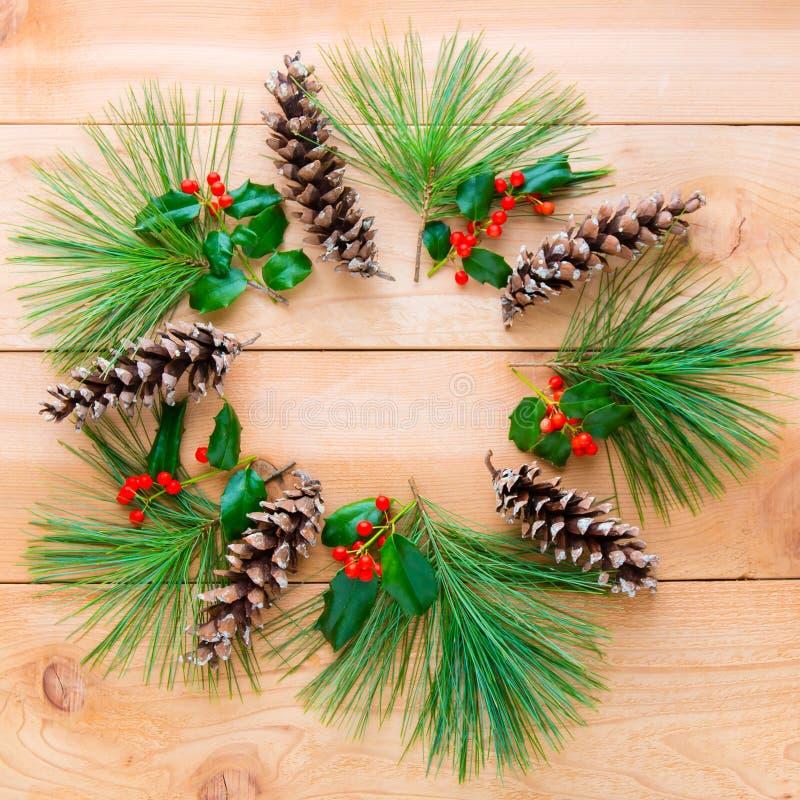 Pigne e rami con la bacca dell'agrifoglio nella forma di wr di Natale immagini stock