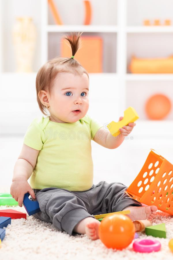 Little baby girl playing with toys royalty free stock photos