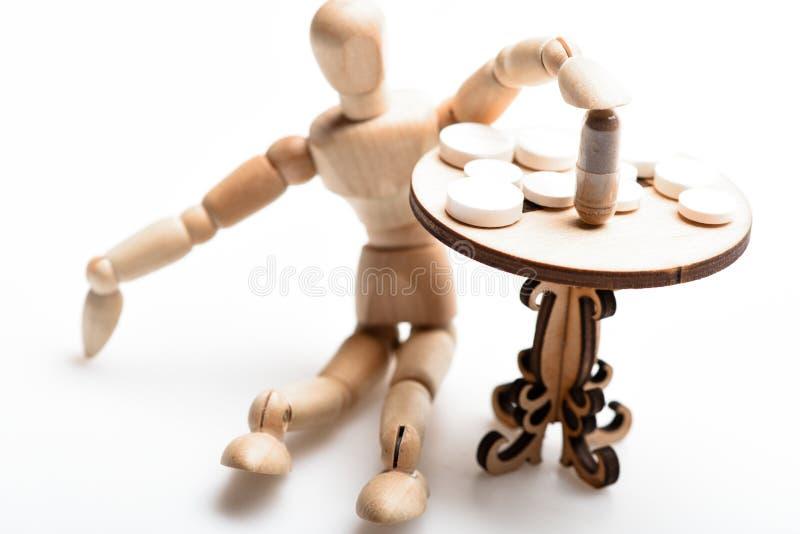 Pigułki na malutkim drewnianym stole Lekarstwo reżim Ludzka drewniana atrapa blisko zgłasza z medycynami Porady brać się do kompl fotografia stock