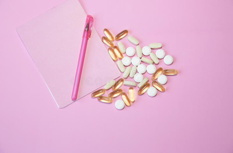 Pigułki, kapsuły i notatnik z piórem na różowym tle z kopii przestrzenią, fotografia royalty free