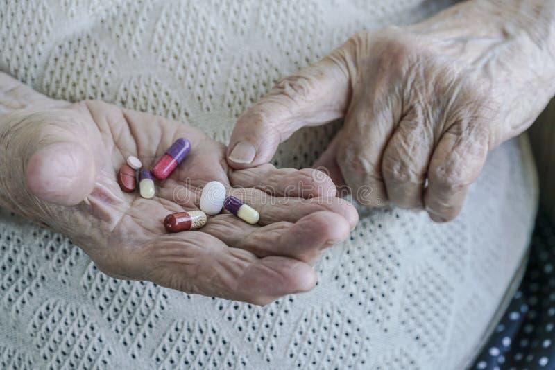 Pigułki na palmie starsza kobieta zdjęcia stock