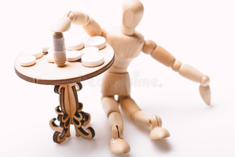 Pigu?ki na malutkim drewnianym stole Lekarstwo re?im Ludzka drewniana atrapa blisko zg?asza z medycynami Porady bra? si? do kompl obrazy royalty free