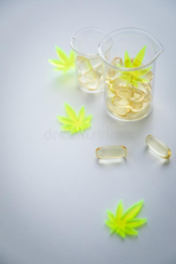 Pigu?ki, pastylki, kapsu?y i medyczny, marihuany marihuany konopie i CBD w lab skali szklanej zlewce jako b?lowy zab?jca obrazy stock
