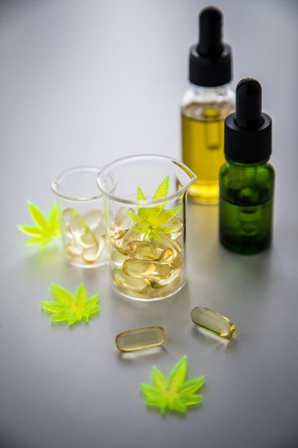 Pigu?ki, pastylki, kapsu?y, olej i medyczny, marihuany marihuany konopie i CBD w lab skali szklanej zlewce jako b?lowy zab?jca zdjęcia royalty free