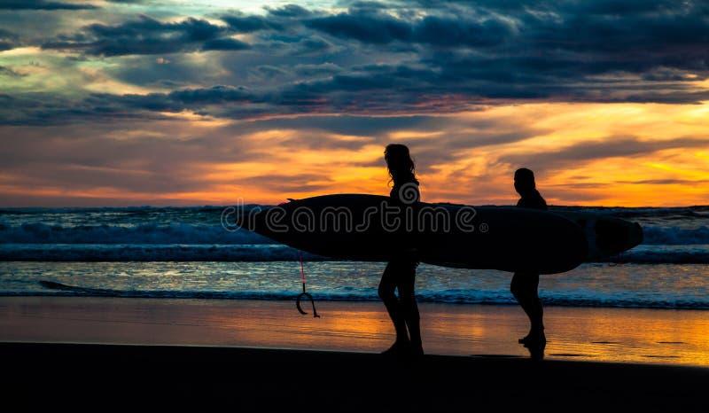 Piha海滩的两位冲浪者在日落 库存照片