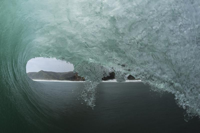 Piha Tube. Piha Beach on Auckland`s West coast is famous for its good surf, this is a POV shot of a surfer`s view inside a tube stock image