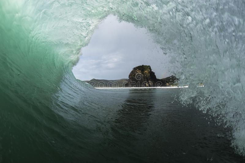 Piha Tube. Piha Beach on Auckland`s West coast is famous for its good surf, this is a POV shot of a surfer`s view inside a tube royalty free stock images