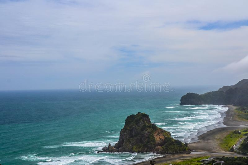 Piha Beach with Lion Rock, New Zealand. New Zeland iconic, famous beaches concept. Panoramic scenic landscape view of surfers popular Piha Beach and Lion Rock in stock photos