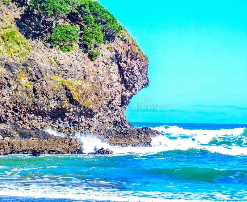 Piha Beach, north Island, auckland, New Zealand. Crashing oceans, high waves, surfing, rock formations, rock out crops, beaches, lion rock royalty free stock photography