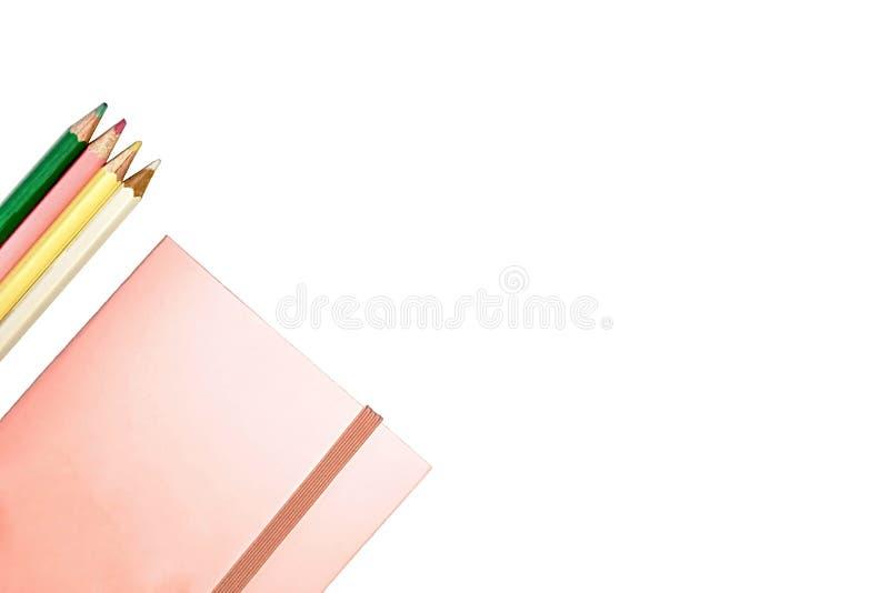 Piinkdocument notitieboekje en vier geïsoleerd kleurenpotloden, stock foto