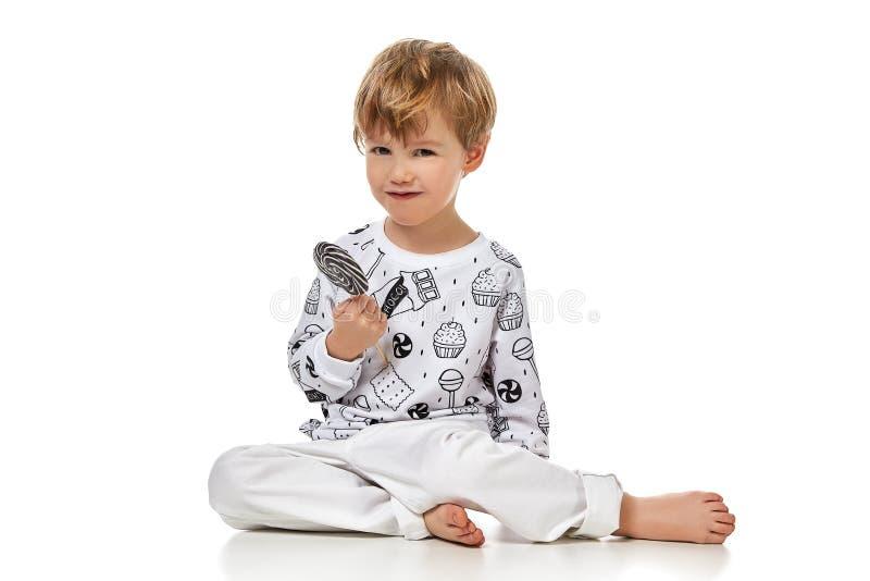 pijama的白肤金发的男婴与candys 免版税图库摄影