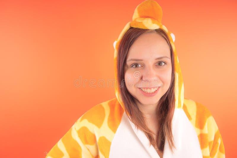 Pijamas bajo la forma de jirafa retrato emocional de una muchacha en un fondo anaranjado mujer loca y divertida en un traje anima foto de archivo libre de regalías