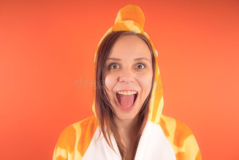 Pijamas bajo la forma de jirafa retrato emocional de una muchacha en un fondo anaranjado mujer loca y divertida en un traje anima fotos de archivo