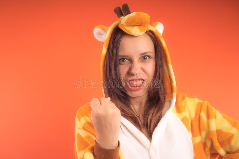 Pijamas bajo la forma de jirafa retrato emocional de una muchacha en un fondo anaranjado mujer loca y divertida en un traje anima foto de archivo