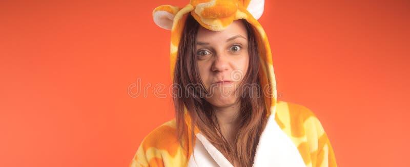 Pijamas bajo la forma de jirafa retrato emocional de una muchacha en un fondo anaranjado mujer loca y divertida en un traje anima imagen de archivo
