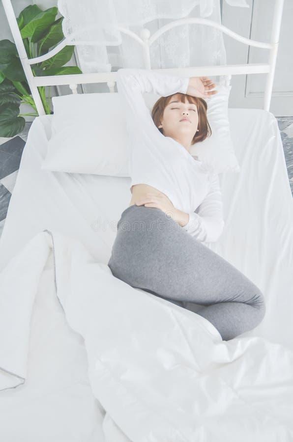 Pijamas blancos de la ropa de mujer en el colchón fotos de archivo