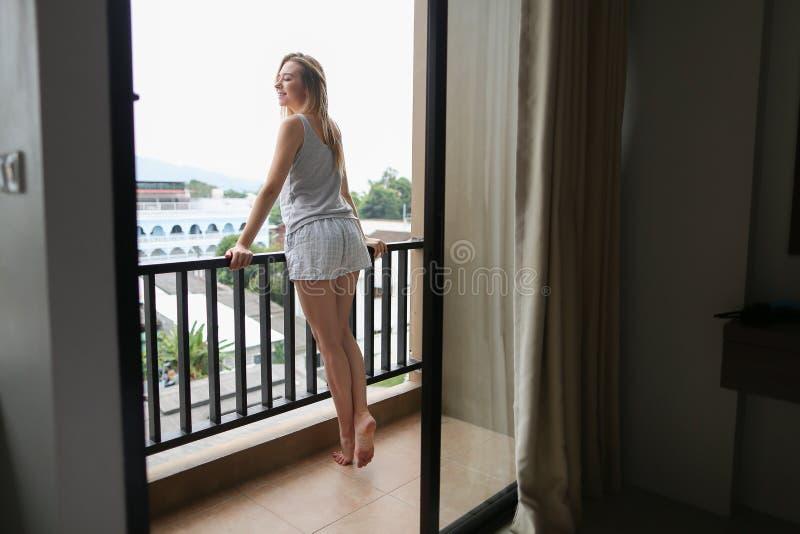 Pijamas del verano de la mujer que llevan bonita joven que se colocan en balcón y que miran edificios fotos de archivo libres de regalías