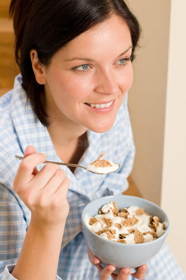 Pijamas felices de la mujer del desayuno casero que comen los cereales fotos de archivo