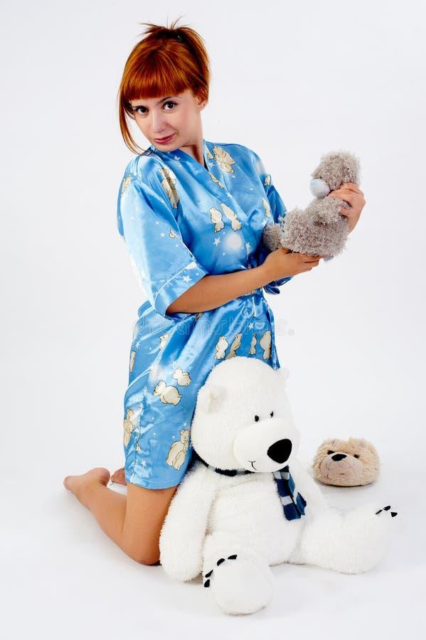 Pijamas que llevan de la muchacha roja bonita con el juguete foto de archivo