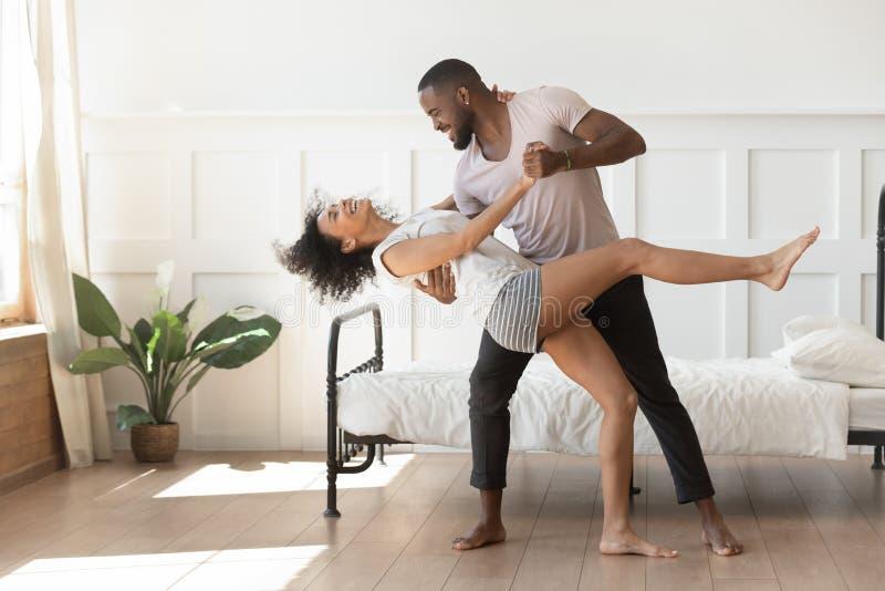 Pijamas que llevan de los pares afroamericanos románticos activos que bailan en dormitorio fotografía de archivo