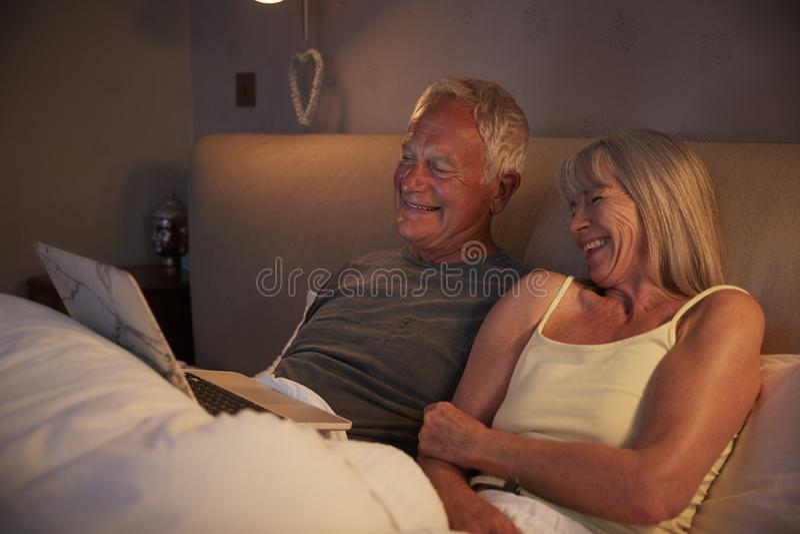 Pijamas que llevan de los pares mayores que mienten en la cama que mira el ordenador portátil foto de archivo libre de regalías