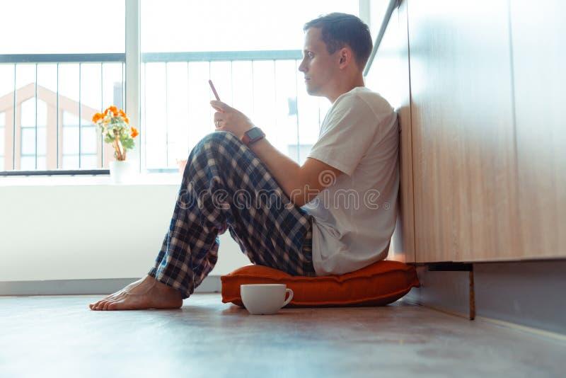 Pijamas que llevan del hombre que se sientan en el piso y que usan smartphone imagenes de archivo