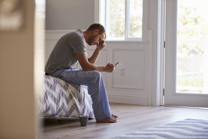 Pijamas que llevan subrayados del hombre usando el teléfono móvil en dormitorio foto de archivo libre de regalías
