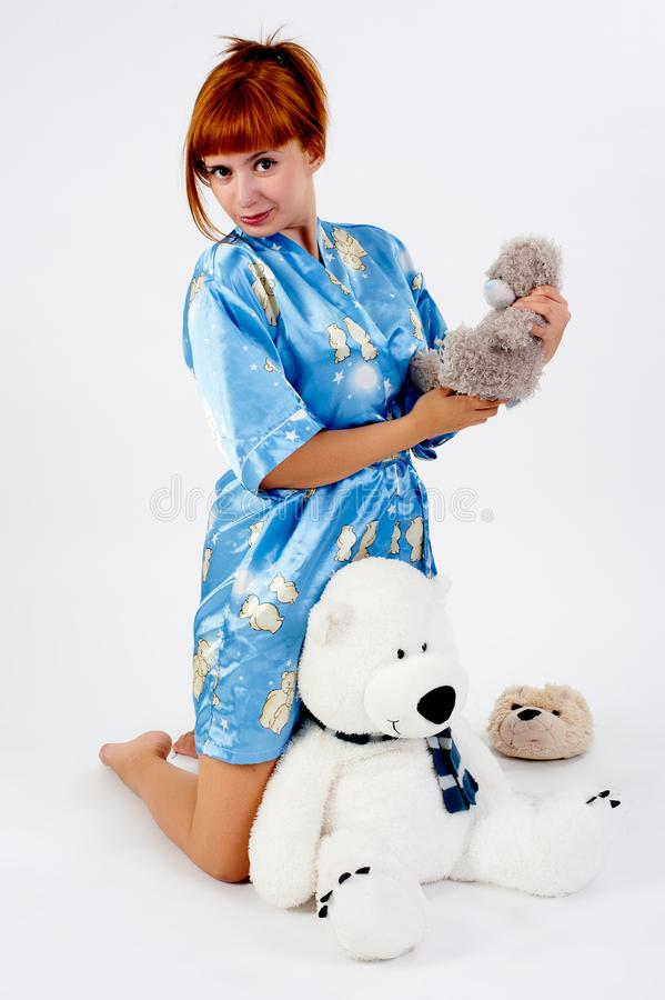 Pijamas vestindo da menina vermelha bonita com brinquedo foto de stock