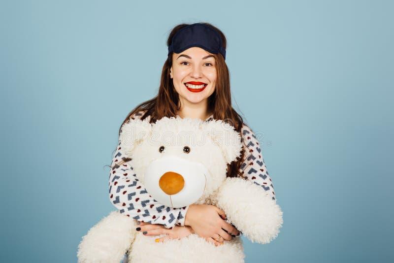 Pijamas vestindo de uma jovem mulher bonita que abraçam seu urso de peluche enchido fotos de stock