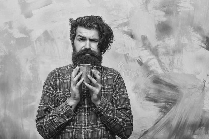 pije gorącej mężczyzna herbaty Nieszczęśliwy brodaty mężczyzna z eleganckiego krana mienia metalu włosianym kubkiem zdjęcia royalty free