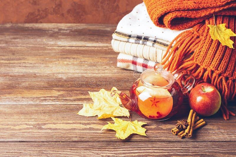 Pije jesieni jabłczane czerwone jagody w szklanej filiżance i czajnik i sterta trykotowy odziewamy na drewnianym tle gor?ca herba obrazy stock