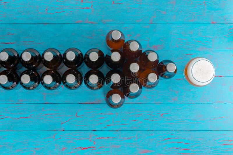Pijl van bierflessen die aan een volledig glas richten royalty-vrije stock afbeeldingen