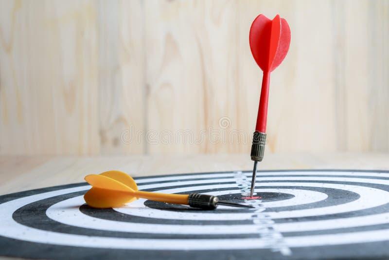 Pijl van het winnaar raakte de Rode pijltje het centrumdoel van dartboard en geel de metafoor van de pijlverliezer marketing de c stock foto's