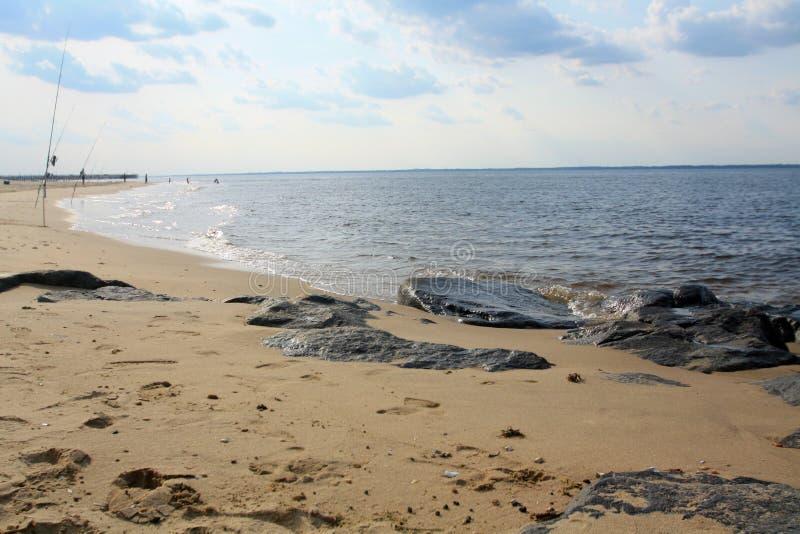 Pijler in de achtergrondwatergolven en sommige Zwarte stenen op kust van het strand in New Jersey stock fotografie