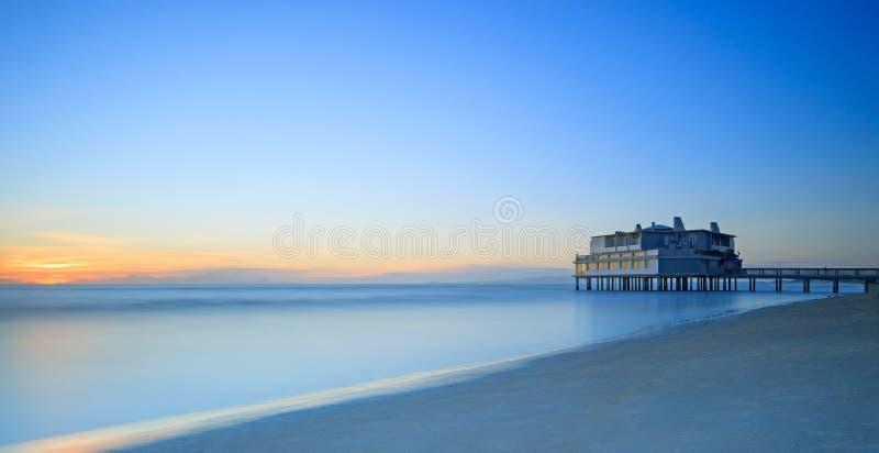 Pijler en het voortbouwen op overzees en strand. Follonica, Toscanië Italië stock afbeeldingen