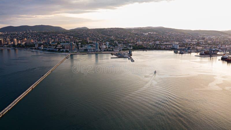 Pijler met een vuurtoren in de stad van Novorossiysk van een hoogte waar u het overzees, de baai bij zonsondergang kunt zien royalty-vrije stock foto's
