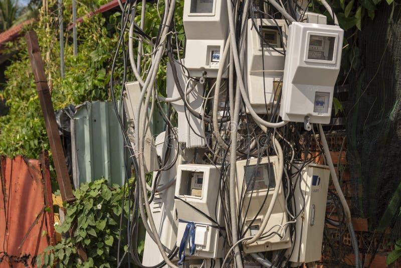 Pijler met elektriciteitsmeters en kabels die wordt overladen stock foto's