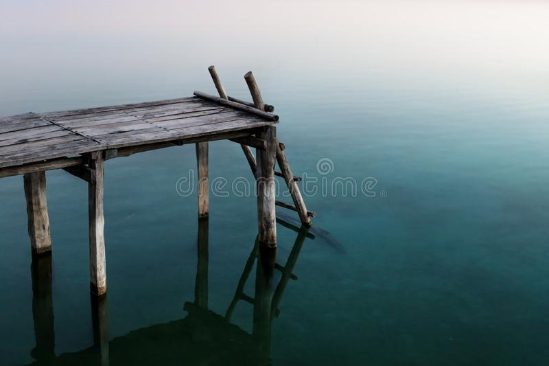 Pijler met ladder met de bezinningen van de zonsondergangkleur in het meer, Gr Remate, Peten, Guatemala royalty-vrije stock foto