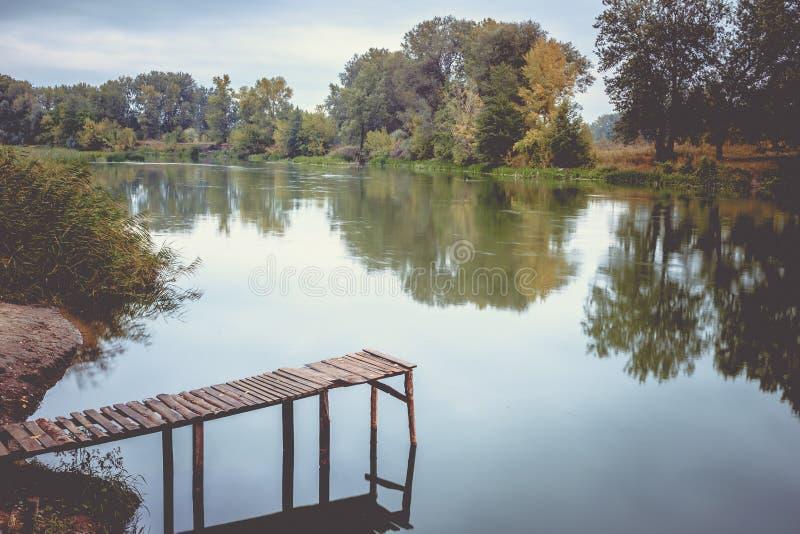 Pijler op een kalme rivier in de zomer Houten pijlerbrug royalty-vrije stock foto's