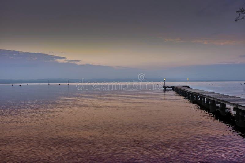 Pijler op Garda-meer, roze zonreeks royalty-vrije stock foto's
