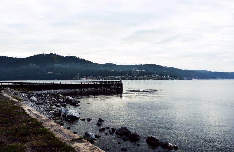 Pijler op het meer in het sombere bewolkte beeld van de weerfoto stock fotografie