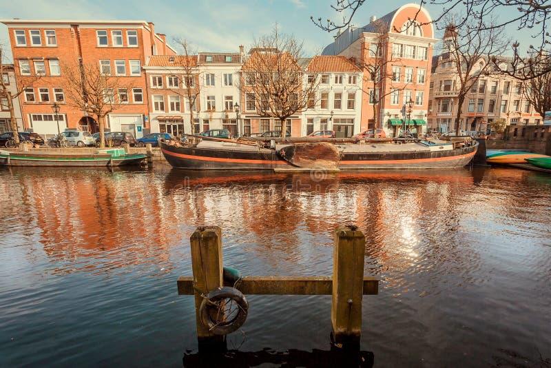 Pijler voor kleine rivierboten bij Nederlands stadskanaal met vastgelegde boten voor vervoer stock foto