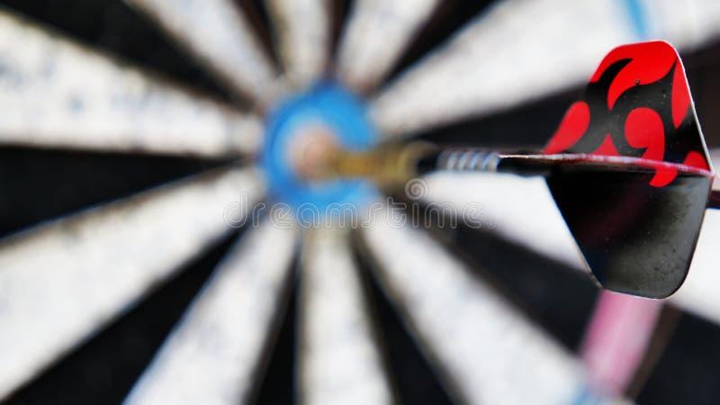 Pijltje op een onscherp oog van doelstieren op de achtergrond stock foto
