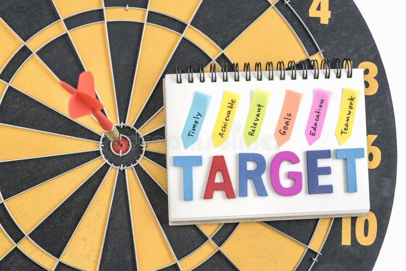 Pijltjedoel in bullseye met woordendoel op het notitieboekje met h stock foto