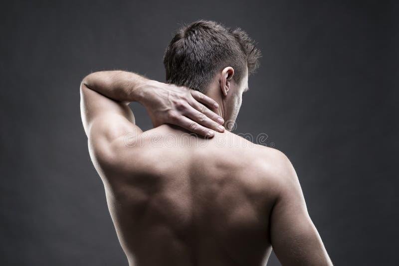 Pijn in de Hals Mens met rugpijn Spier mannelijk lichaam Het knappe bodybuilder stellen op grijze achtergrond Rustige dichte omho royalty-vrije stock afbeeldingen