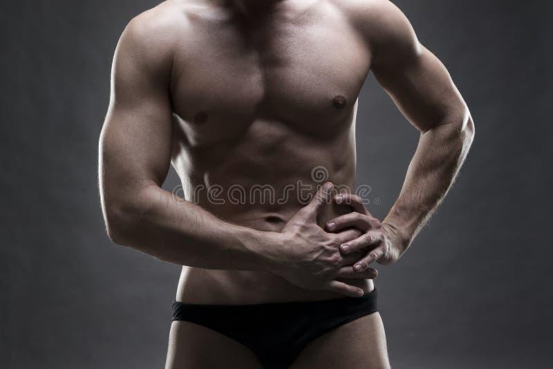 Pijn in de linkerkant van het spier mannelijke lichaam Het knappe bodybuilder stellen op grijze achtergrond Rustig dicht omhoogga stock fotografie