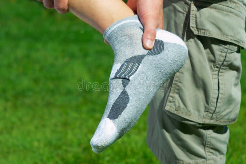 Pijn in de voet, voeten op de achtergrond van groen gras stock foto