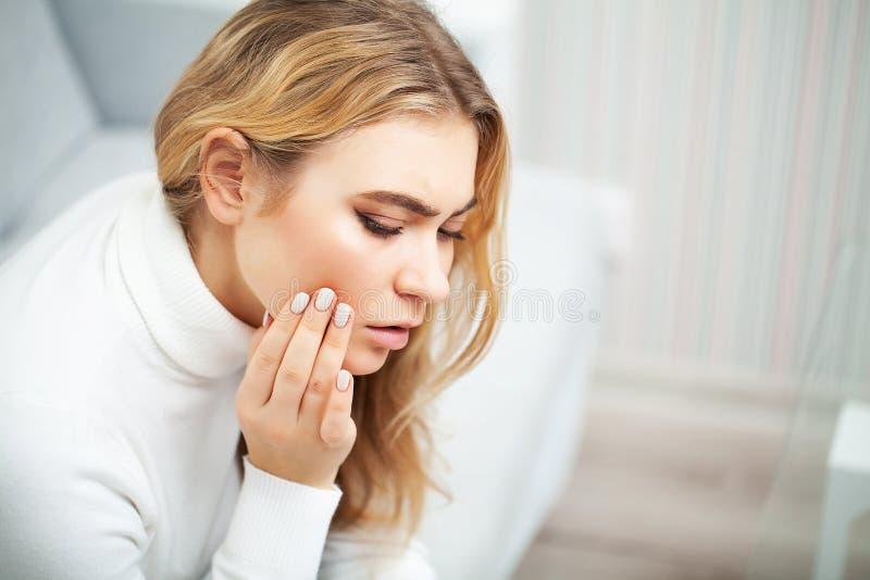 pijn Het probleem van tanden Een vrouw voelt pijn in haar tand Een beeld van een mooi, droevig meisje die aan streng lijden stock foto's
