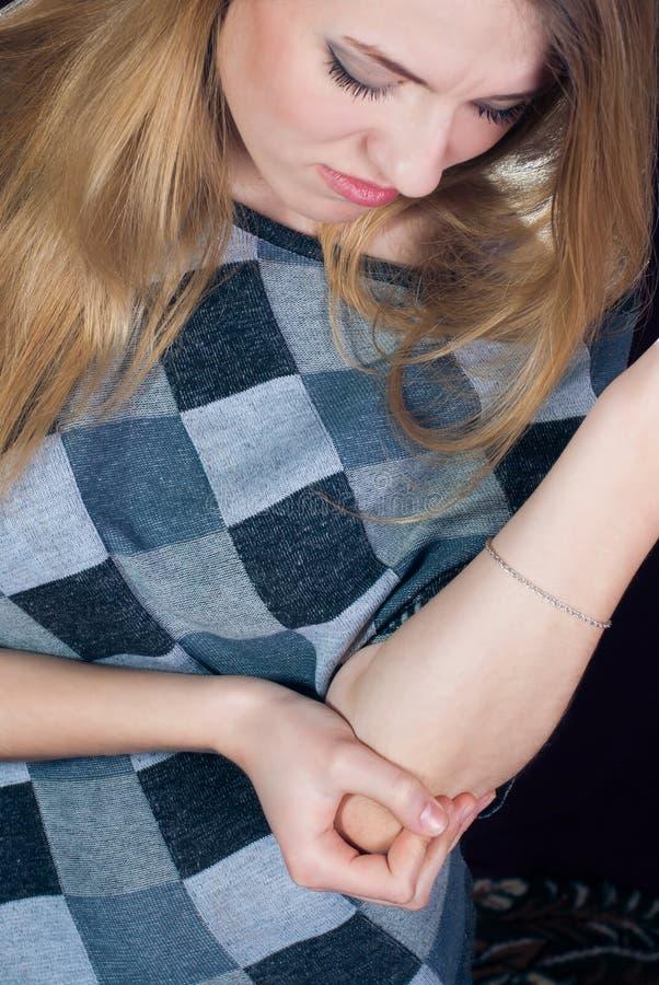 In Pijn, jonge vrouw die haar elleboog houdt stock foto's